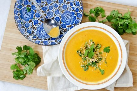 orange carrot ginger soup with peanut cilantro herb garnish on top